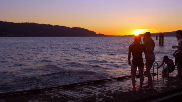 teenagers jumping from dock into lake at sunset - badeshorts stock-videos und b-roll-filmmaterial