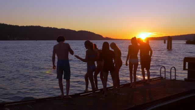teenagers jumping from dock into lake at sunset - badbyxor bildbanksvideor och videomaterial från bakom kulisserna