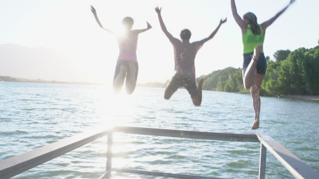 ws rv teenagers jumping into a lake together - jetty stock videos & royalty-free footage