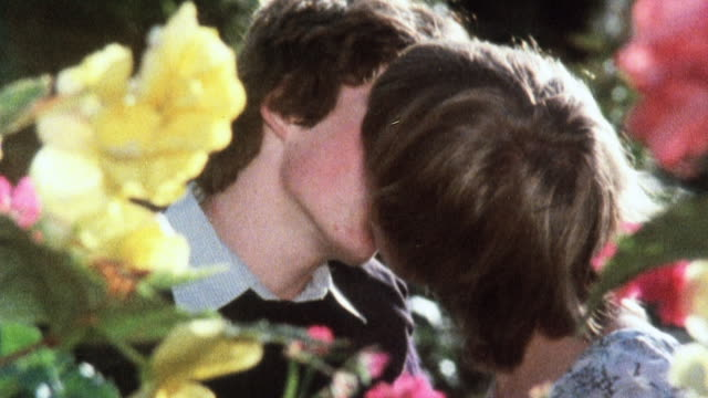 1981 cu teenagers kissing in a flower garden / united kingdom - kissing stock videos & royalty-free footage
