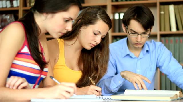 vidéos et rushes de adolescents de formation ensemble à l'intérieur de la bibliothèque - littérature