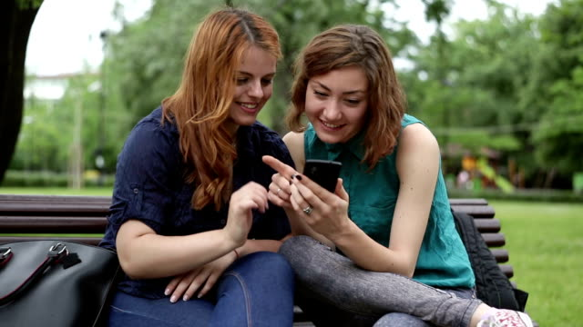 Teenagers looking pictures on a cell phone