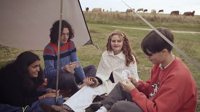 teenagers messing about playing a game of cards on a camping trip - escapism stock videos & royalty-free footage