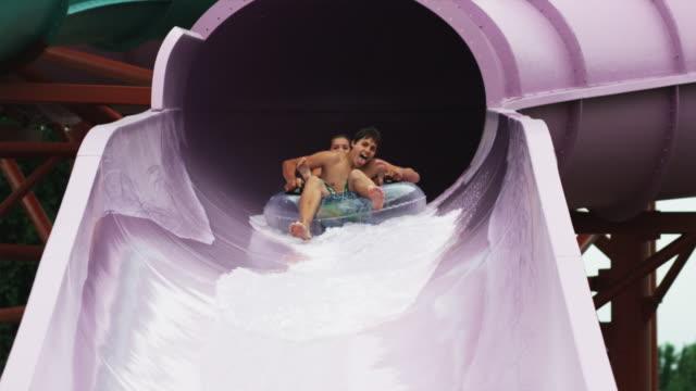 teenagers on a waterslide - water slide stock videos & royalty-free footage
