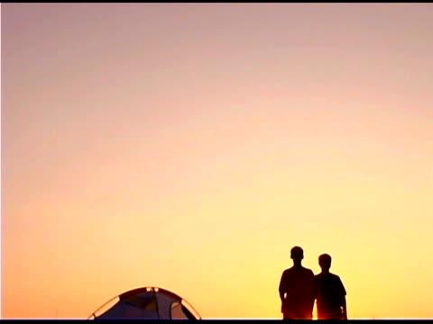 teenagers on beach by tent at sunset - 少年だけ点の映像素材/bロール