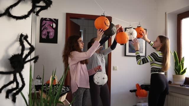 stockvideo's en b-roll-footage met teenagers putting up halloween decorations in a hallway - driekwartlengte