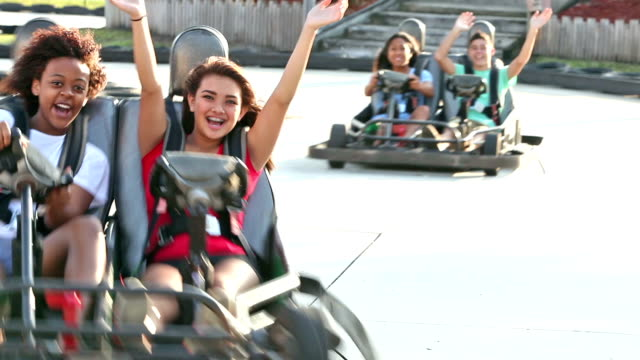 Teenagers riding go-carts at amusement park