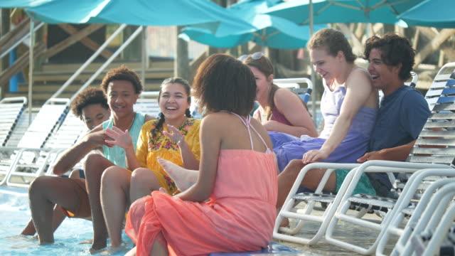 jugendliche sitzen auf liegestühlen, pooldeck - multi ethnic group stock-videos und b-roll-filmmaterial
