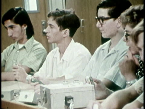 vidéos et rushes de 1973 ms teenagers sitting in a row, teacher asking questions, students buzzing in to answer / united states - demander