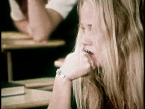 1973 MONTAGE teenagers sitting in classroom, looking bored, teacher talking to them about assignment, bell ringing, kids standing up to leave / United States