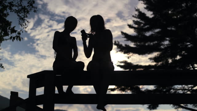 LA Teenagers sitting on fence and taking photos of each other at sunset / Stowe, Vermont, United States