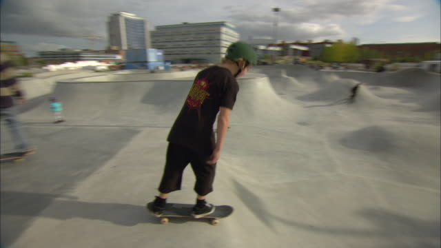ws pan teenagers skateboarding at skate park / malmo, sweden - helm stock-videos und b-roll-filmmaterial