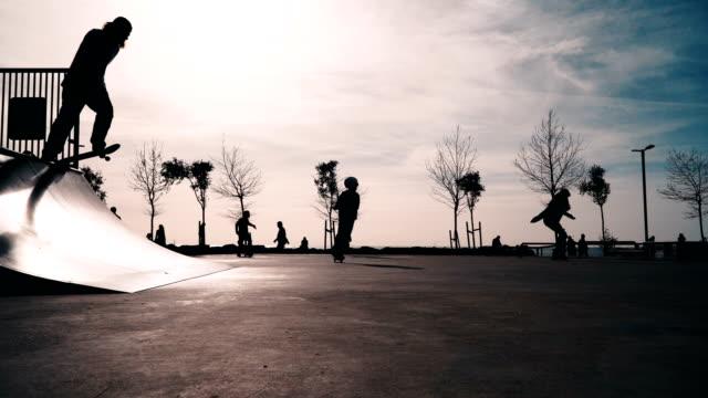 jugendliche, skateboarding, rollern und radfahren auf städtischen skatepark - skateboard park stock-videos und b-roll-filmmaterial