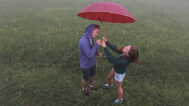 teenagers stand under umbrella in meadow, sharing music - music stand stock videos & royalty-free footage
