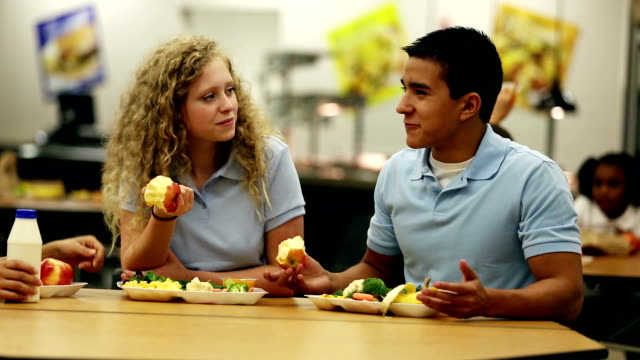 teenagers talking over lunch in school cafeteria - canteen stock videos & royalty-free footage