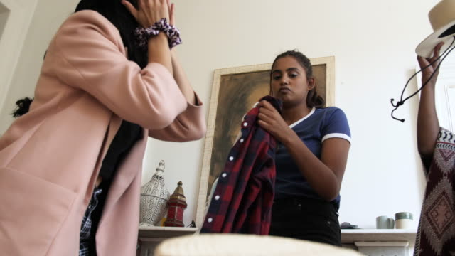 stockvideo's en b-roll-footage met teenagers try on different clothes, slow motion - moving past