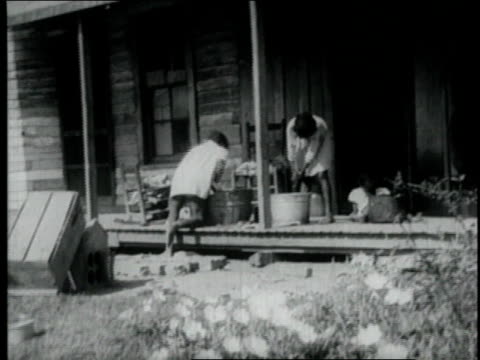 1940 MONTAGE teenagers washing clothes by hand on a porch / United States