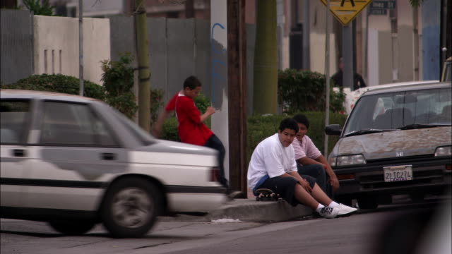 teenagers watch a boy fall off his skateboard on an urban street corner. - off stock videos & royalty-free footage