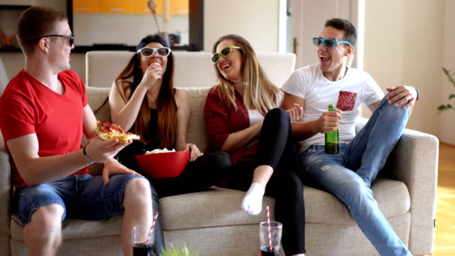 Teenagers watching funny 3D movie at home
