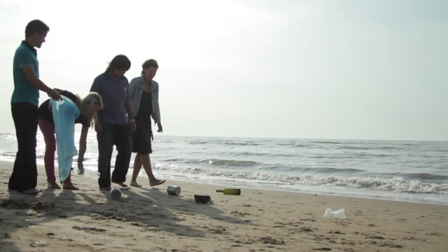 Teenagers with adult Volunteering Beach Cleanup