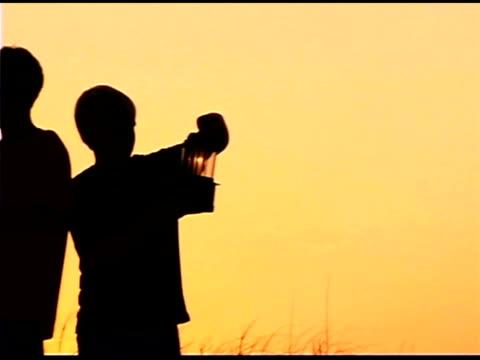 teenagers with lanterns at sunset - 少年だけ点の映像素材/bロール