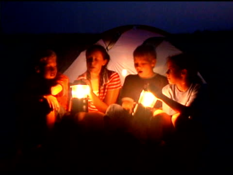 teenagers with lanterns by tent at night - ランタン点の映像素材/bロール