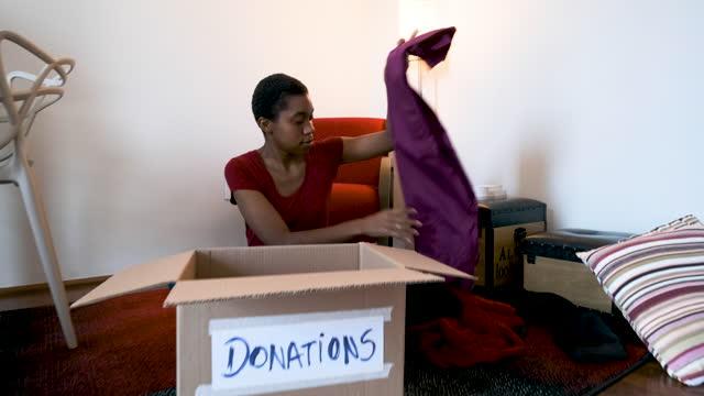 vídeos y material grabado en eventos de stock de chica adolescente con el pelo corto que se pone ropa para la donación. - sólo mujeres jóvenes