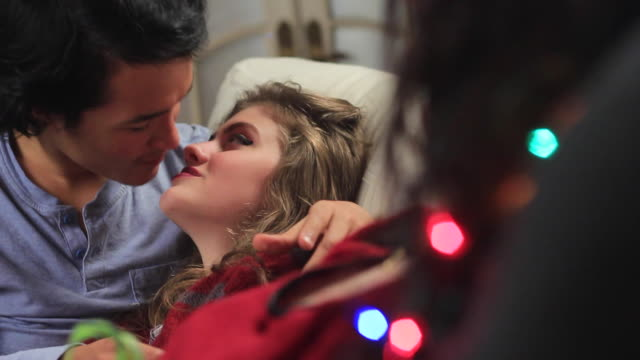 Teens Christmas kiss on couch