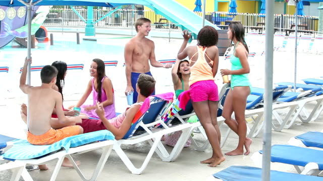 Teens hanging out together on pool deck lounge chairs