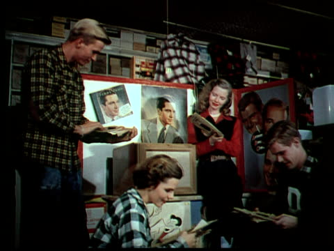 1949 MS Teens in flannel shirts looking at Perry Como records at department store display