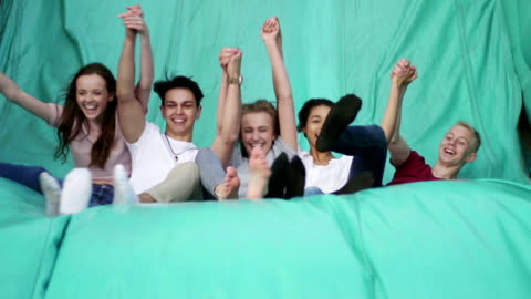 teens jumping down a slide at fairground - teenagers only stock videos & royalty-free footage