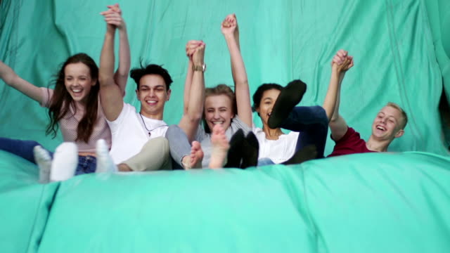 Teens Jumping Down a Slide at Fairground