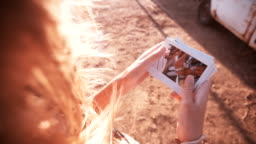 Teens looking at instant photos outdoors on summer afternoon