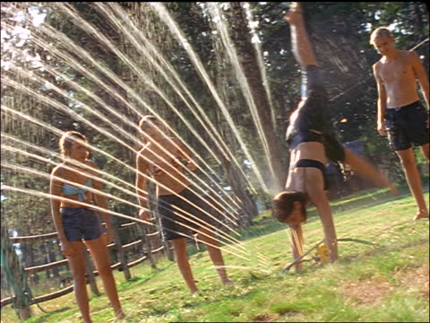 teens playing in sprinkler outside / montana - 1999 stock videos & royalty-free footage