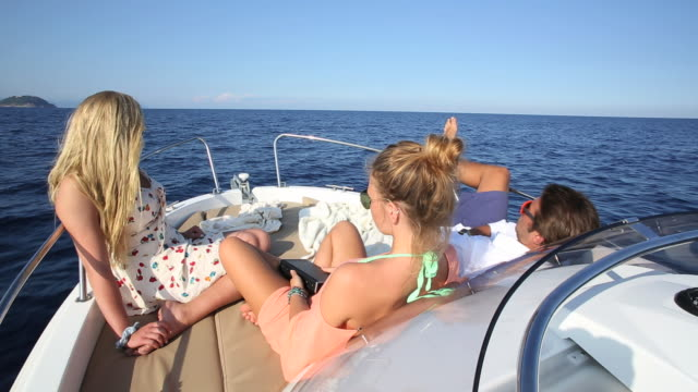teens relax on power boat, tranquil sea - power boat stock videos & royalty-free footage
