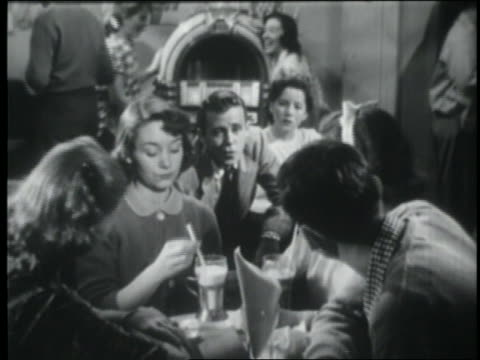 vidéos et rushes de b/w 1951 teens sitting at table in malt shop / boy from neighboring table talks to them - milk shake