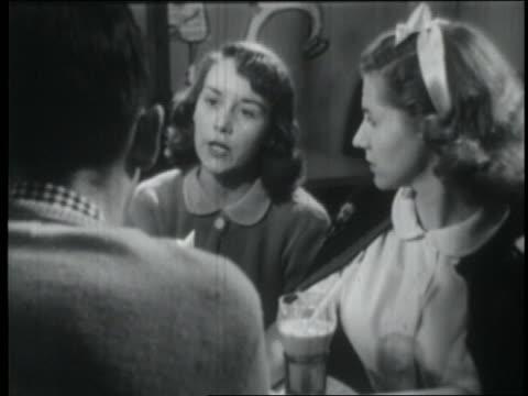 vídeos de stock e filmes b-roll de b/w 1951 teens sitting at table in malt shop / one girl talking - 1951