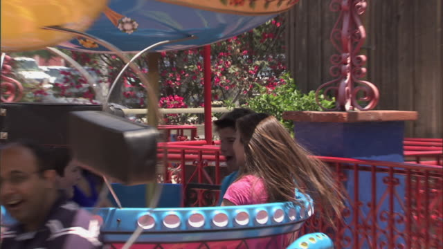 Teens spinning and laughing on Mexican Hat Dance ride at Knott's Berry Farm