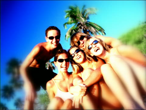 vídeos de stock e filmes b-roll de overexposed canted portrait teens + young adults in sunglasses sit on beach laughing / seychelles - super exposto