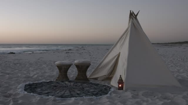 vídeos y material grabado en eventos de stock de teepee and wicker stools at beach during sunset - tienda de campaña