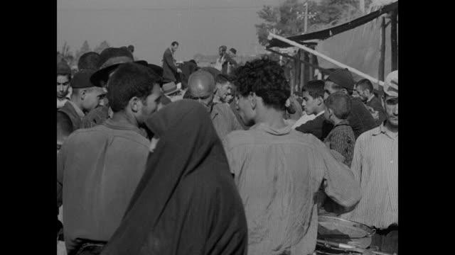tehran oldworld cityscapes people walking on sidewalks w/ open gutters fg iranian man washing face in open gutter water open air bazaar people buying... - iran bildbanksvideor och videomaterial från bakom kulisserna