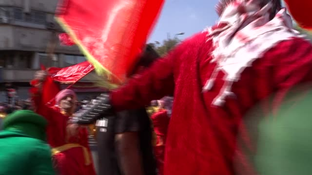 stockvideo's en b-roll-footage met tehran skyline and day of ashura commmemoration procession with flags / men in red uniforms chase anonymous children in green costumes pretend to... - startvlag