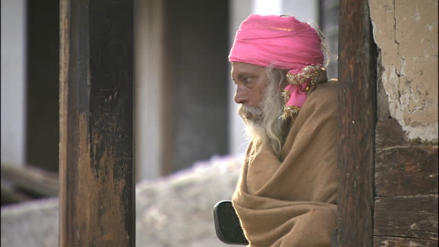 tehri dam gangotri and himalayas man in pink turban seated looking into camera/ man seated in hut sorting through notes/ bells hanging from frame... - religious music stock videos and b-roll footage