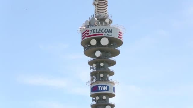 a telecom italia spa and tim transmission tower stands in rome pedestrians pass a tim store the mobile phone unit of telecom italia spa tilt down... - attrezzatura per le telecomunicazioni video stock e b–roll