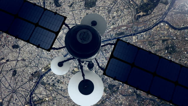 telecomunication satellite sending signal to earth. flying over large city - satellite video stock e b–roll