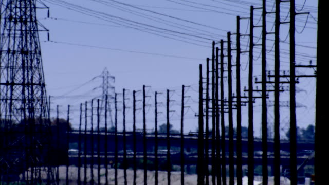 telegraphs and pylons line a highway in los angeles. available in hd. - telegraph pole stock videos and b-roll footage