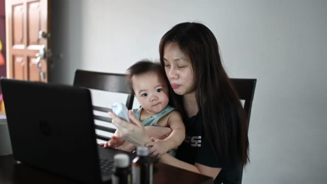 vídeos de stock e filmes b-roll de telemedicine asian  chinese mother checking her baby boy son body temperature using thermometer while consulting her pediatrician doctor online using laptop - cold temperature
