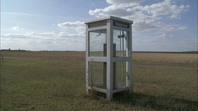 ws telephone booth in field, voves, beauce, france - 電話ボックス点の映像素材/bロール