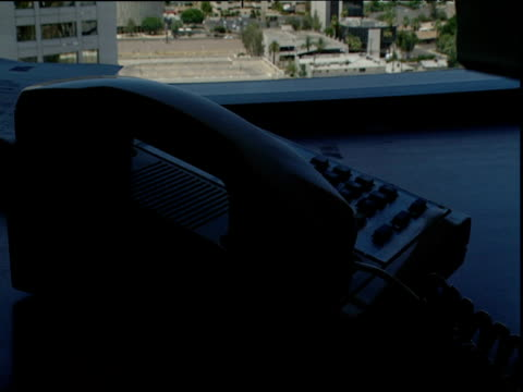 Telephone directory is placed on desk in unlit office and hand picks up telephone handset and dials number with office buildings visible through window in background California
