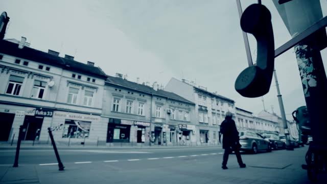stockvideo's en b-roll-footage met telefoonhoorn met straat verkeer op de achtergrond - telefooncel